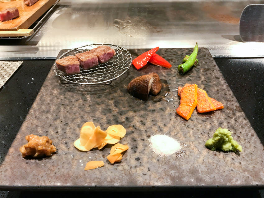 A square stone plate with some vegetables and kobe beef cooked and served, along with some condiments