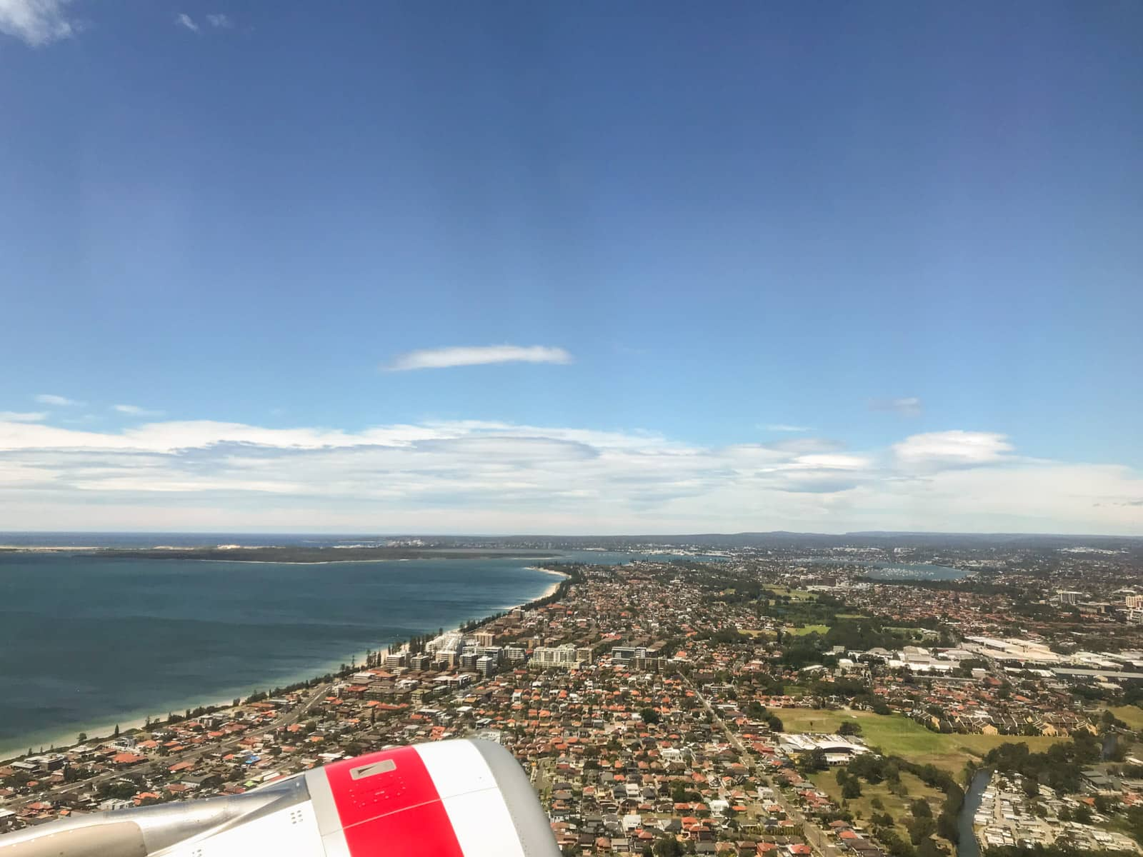 The view from the side of a plane, of the city of Sydney. It is during the day and the sky is blue