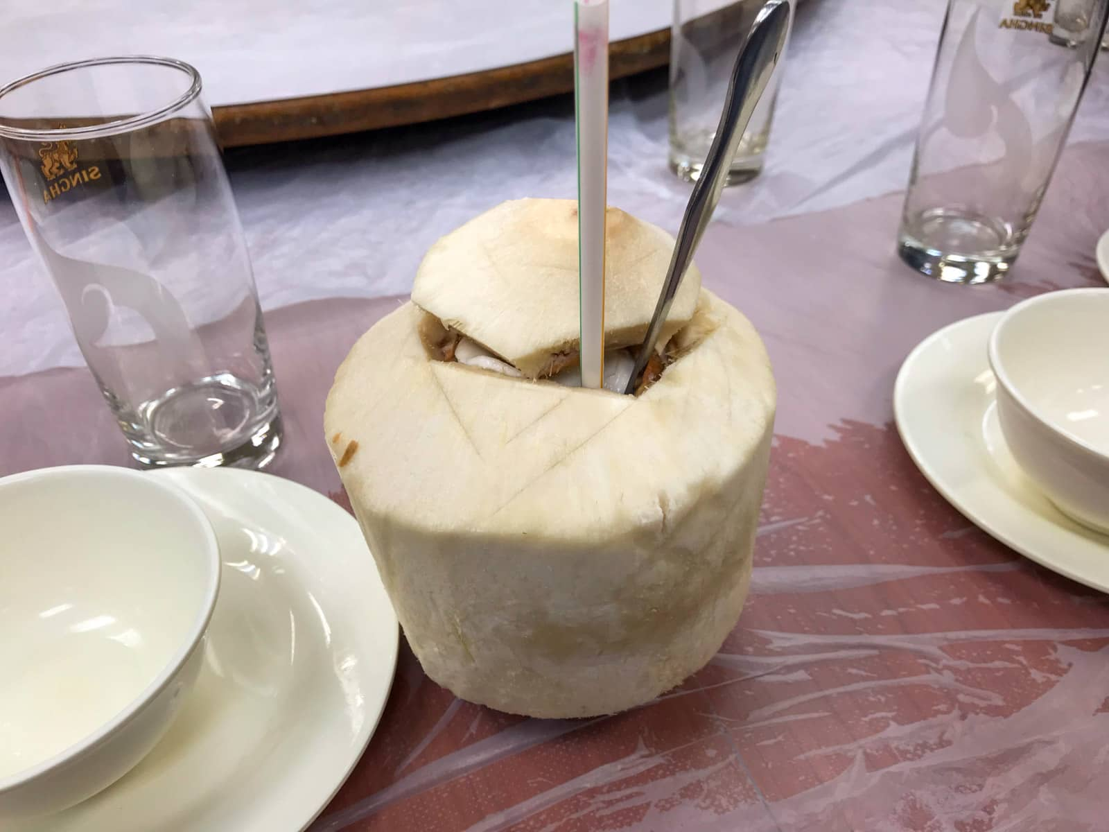 A primitive dining table setting, with a coconut with the top sliced open. It has a straw and spoon sticking out of the top if it.