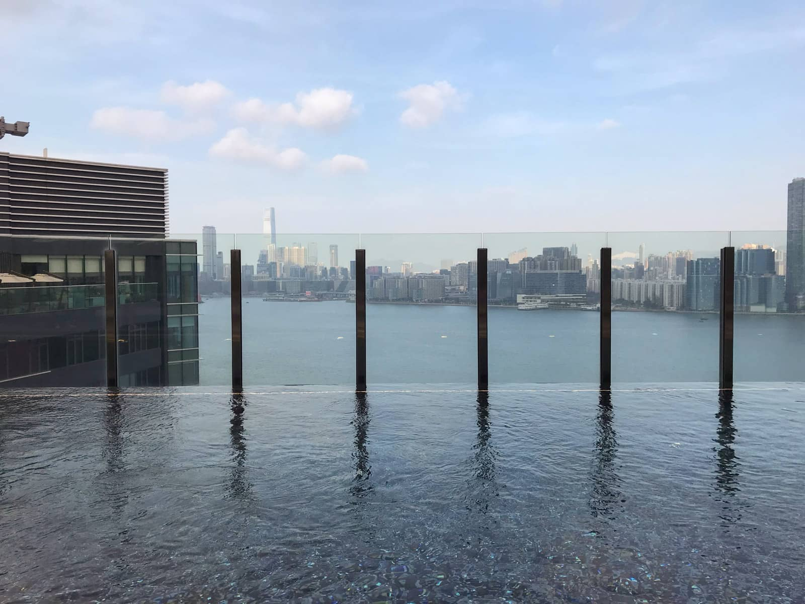 The view of an infinity pool from the water side, showing a view of Hong Kong through the glass at the end of the pool
