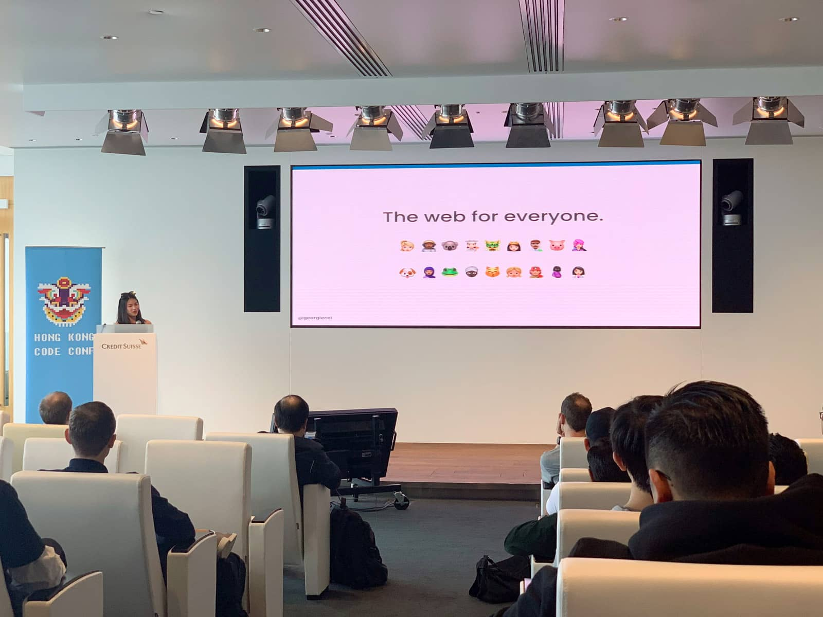 "The inside of a conference room with a wide screen showing ""The web for everyone"" and a number of different emoji to represent diversity. A woman stands at a podium at the front of the room on a stage."