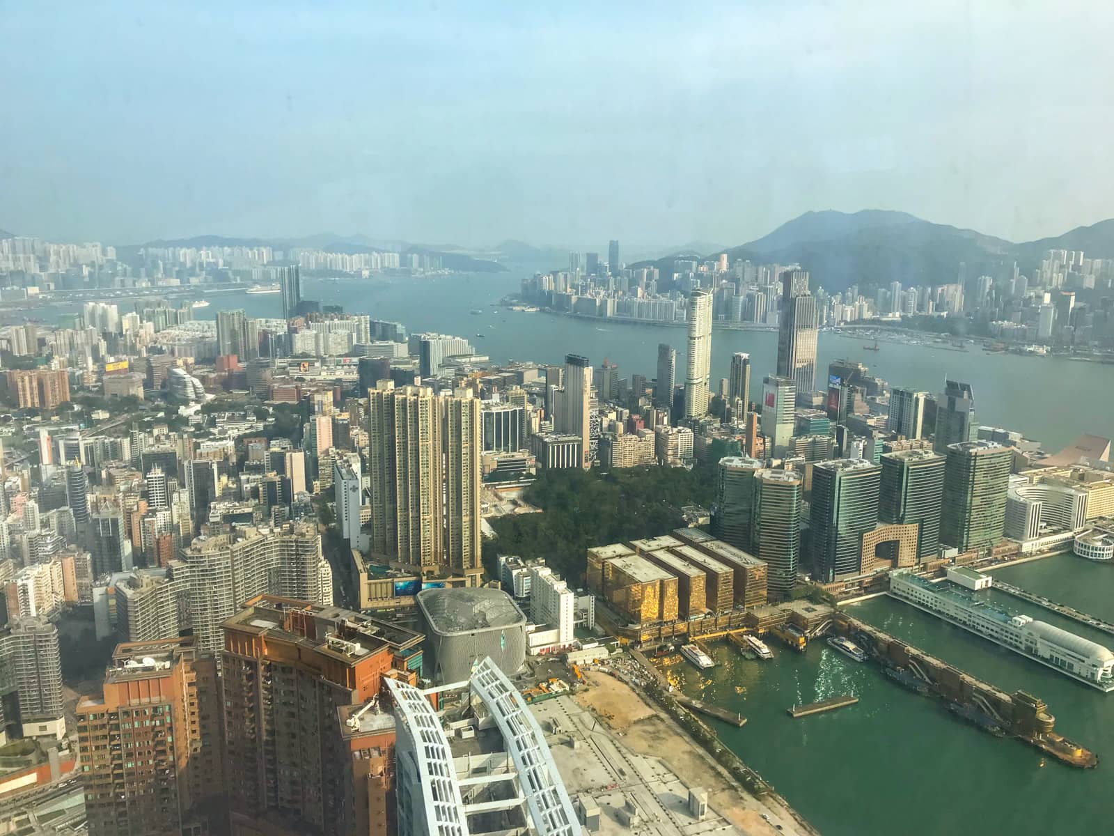 A view of the city of Hong Kong, with the harbour and many buildings visible, seen from the inside of a glass window at a high vantage point