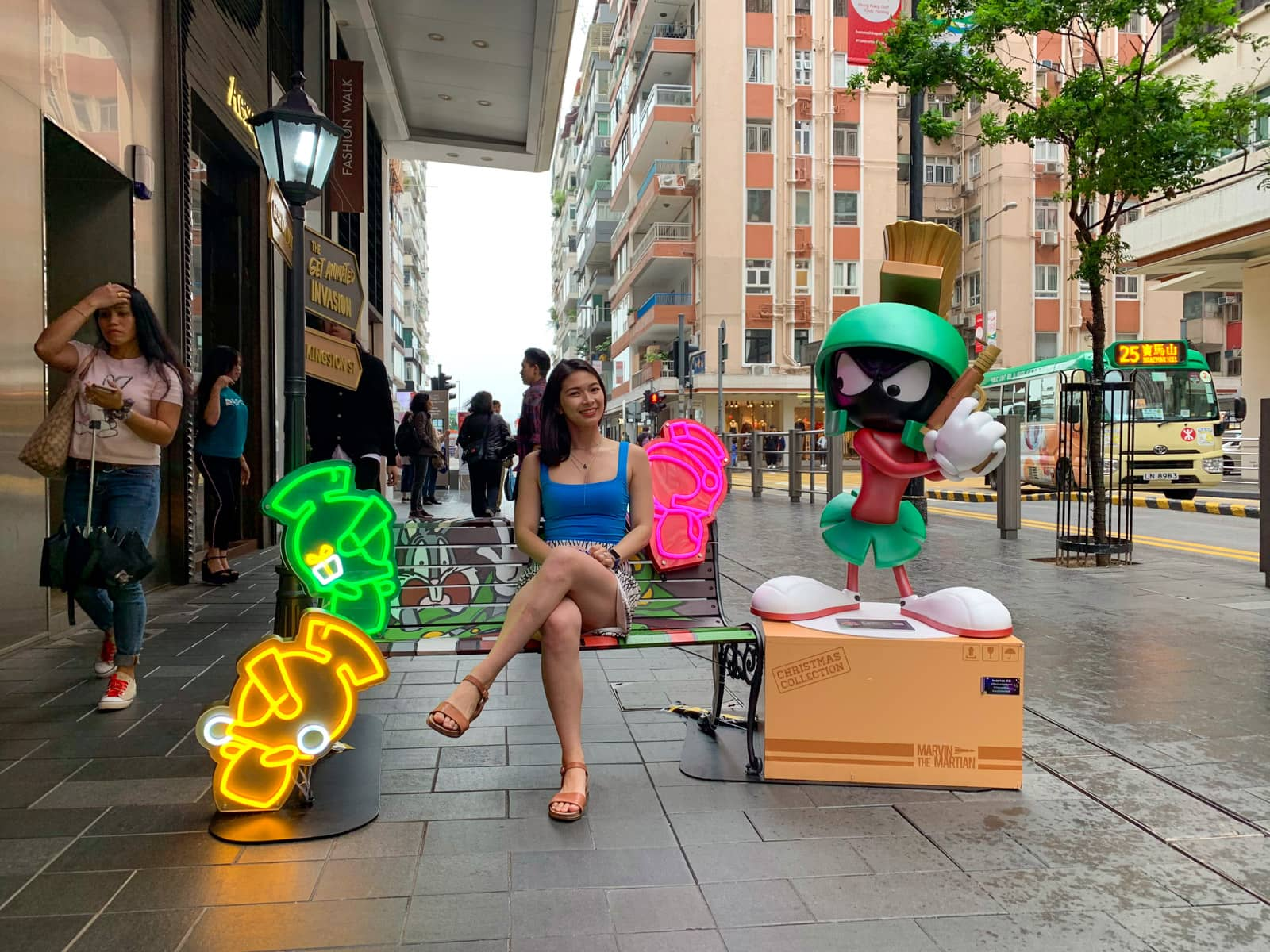 A woman sitting on a Looney Tunes stylised bench. A life size statue of the Marvin the Martian character is sitting next to the bench