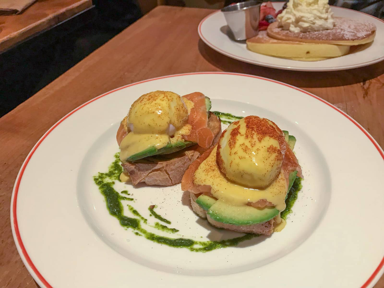 Salmon eggs benedict served on a plate (poached egg with hollandaise sauce, with smoked salmon and avocado on toast)