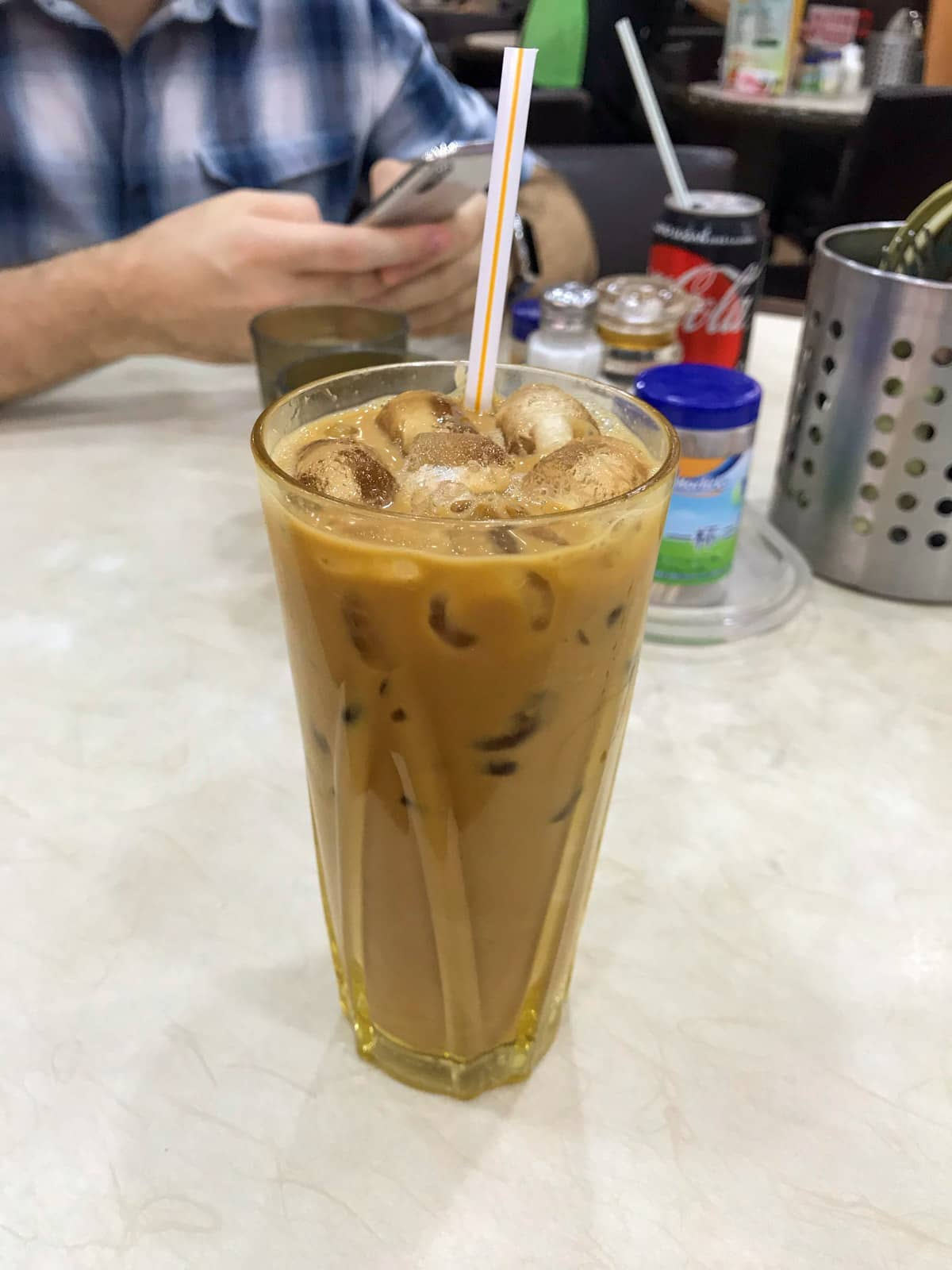 A tall glass of Hong Kong milk tea, which is iced and has a tan brown colour to it