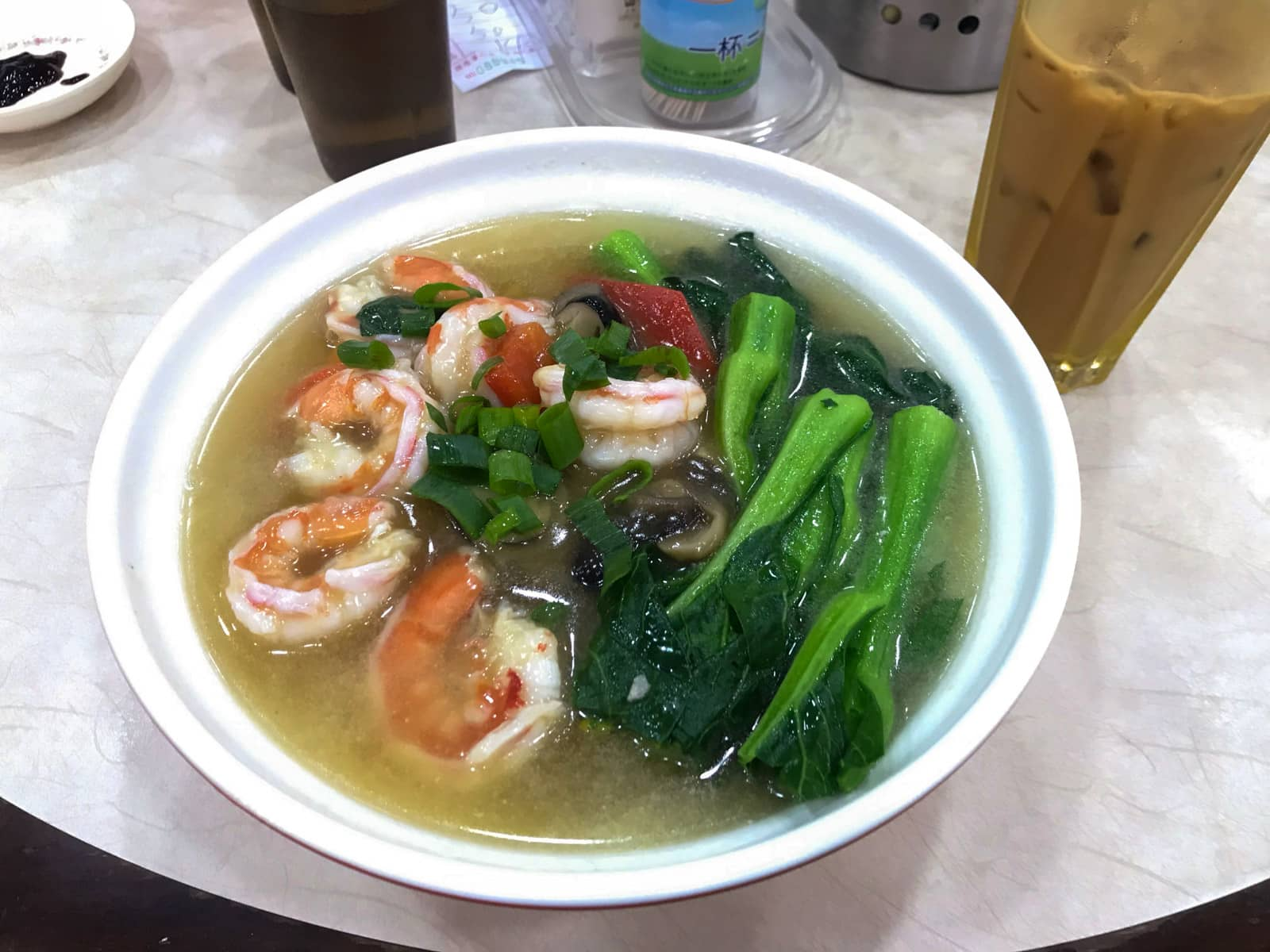 A bowl of soup with Asian greens, many prawns and some other vegetables