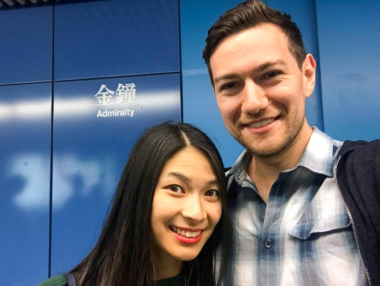 "A man and woman with dark hair, smiling. They are taking a selfie in front of a blue wall with ""Admiralty"" written in English and in Chinese symbols."