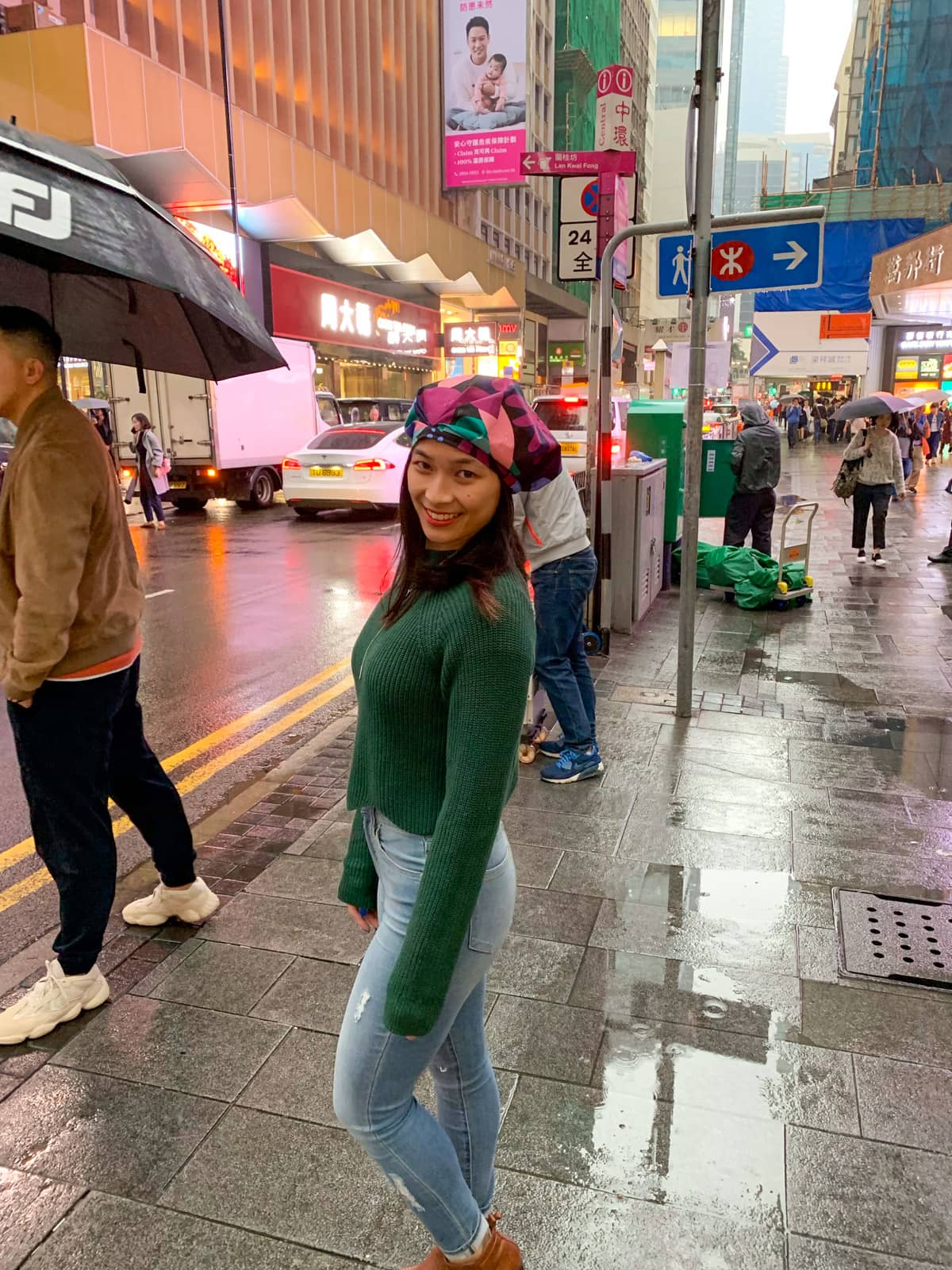A woman wearing a dark green jumper and light blue jeans and brown boots, with a brightly coloured showercap on her head. She is outside in the rain in a street in Hong Kong