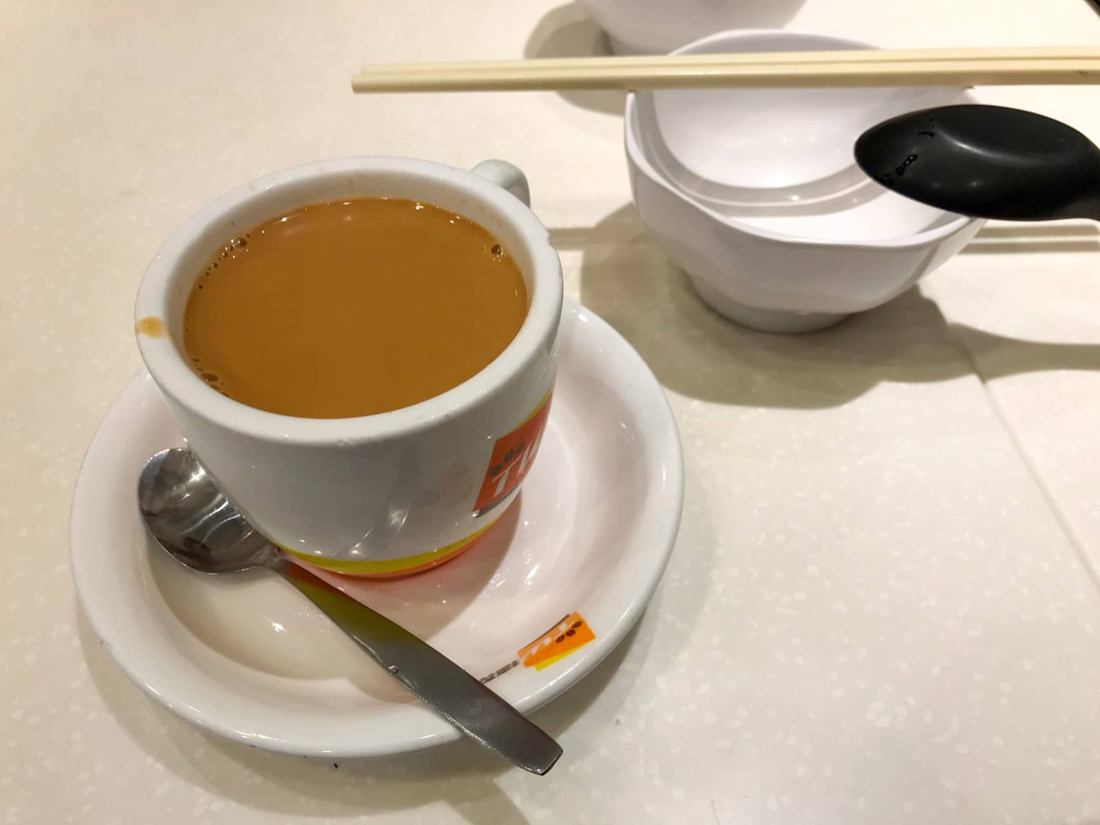 A small white cup of Hong Kong style milk tea, served on a small saucer