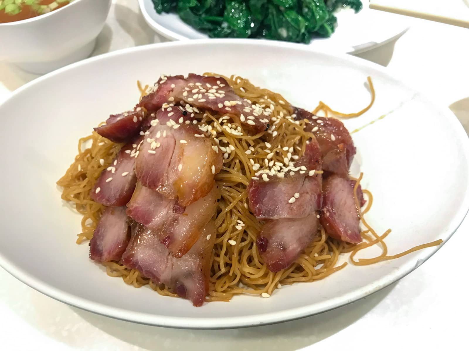 A white bowl of stir-fried noodles served with slices of roast pork, topped with sesame seeds.