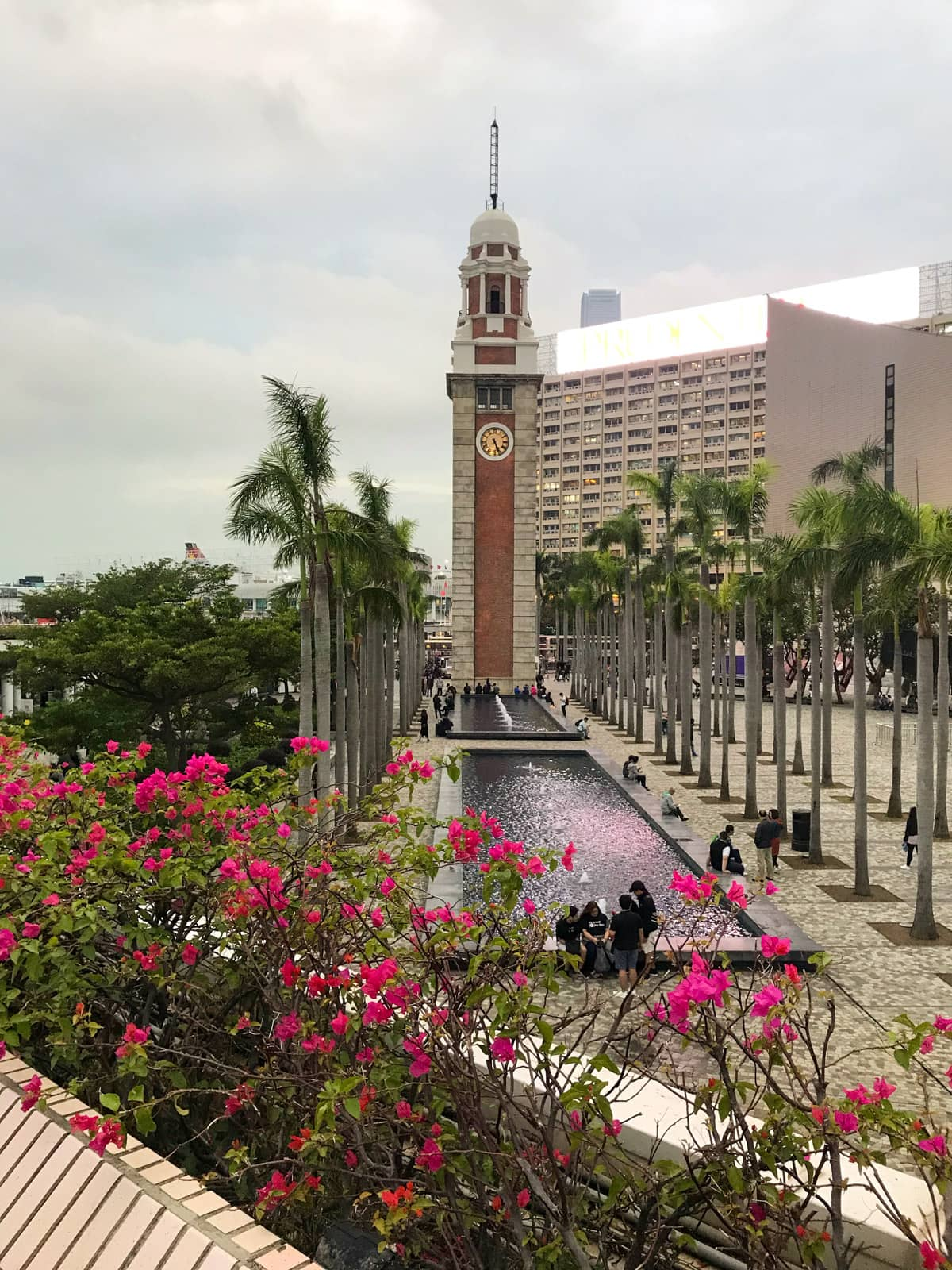 A tall tower with a long water feature in front of it. Palm trees adorn the sides of the water feature. The sky is cloudy and muted in colour.