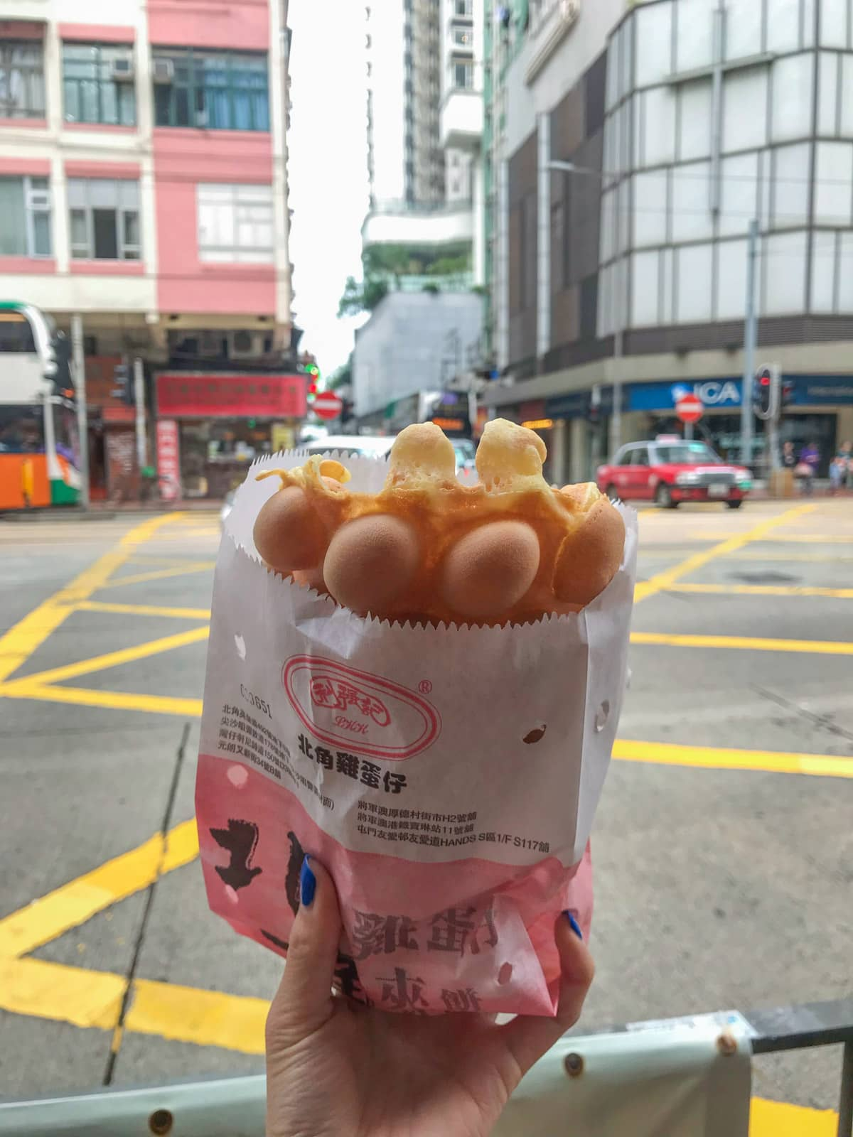A woman's hand holding a paper bag with a Hong Kong style egg waffle in it, having the texture of hemispheres