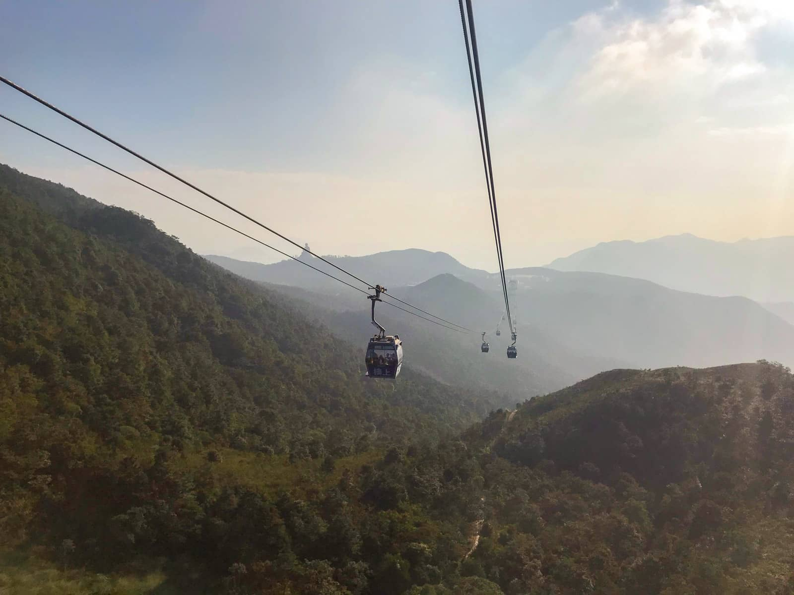 A view of two lines of cable cars going in opposite directions as seen from another cable car on the route