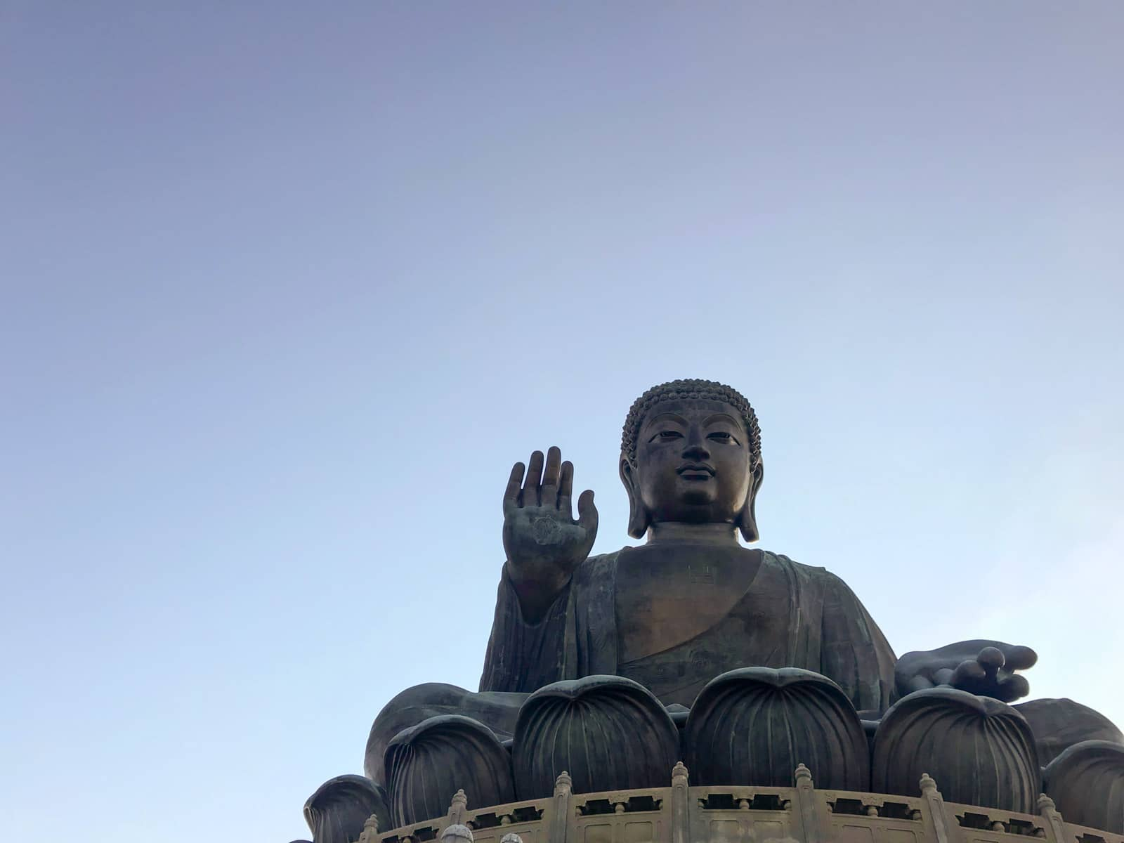 A very large Buddha statue from a low angle. The sky is clear and blue but it is dusk