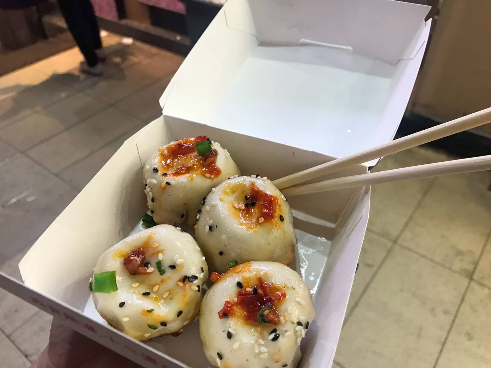 A cardboard box of four pan-fried pork dumplings seasoned with sauce. Wooden disposable chopsticks stick out the side of the box