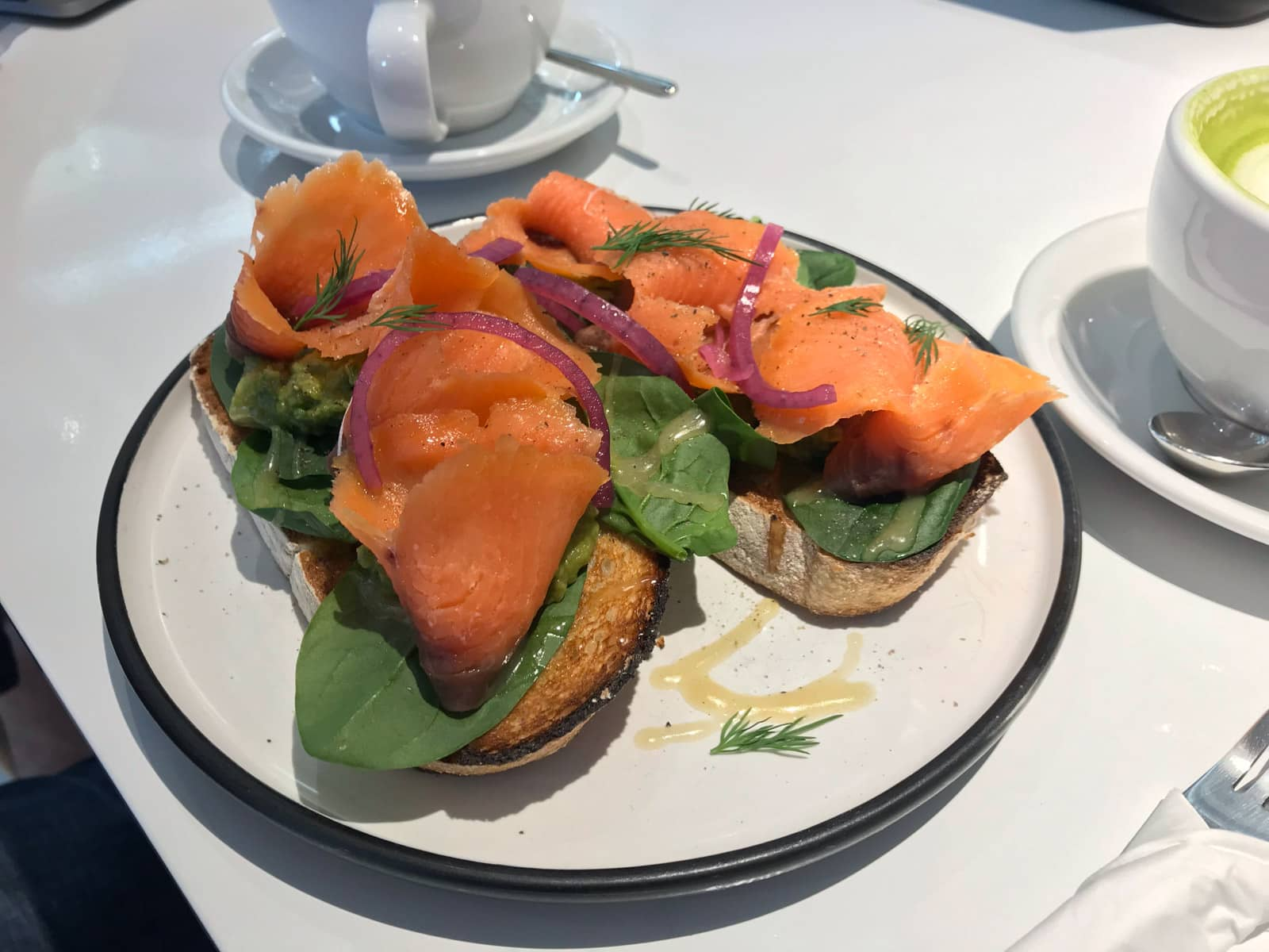 Smoked salmon with spinach served with onion on toasted bread, presented on a round white dish.