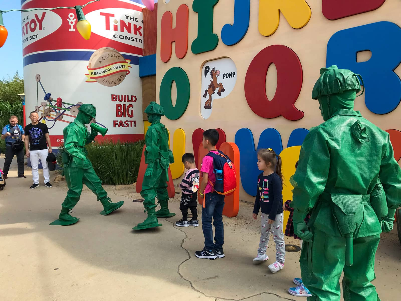 The inside of a theme park with some people dressed in character as life-sized green soldier figurines. A wall with colourful letters of the alphabet sit on the side.