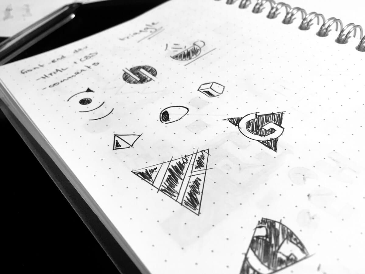 A dot grid spiral bound notebook with various logo sketches, most of which are triangles