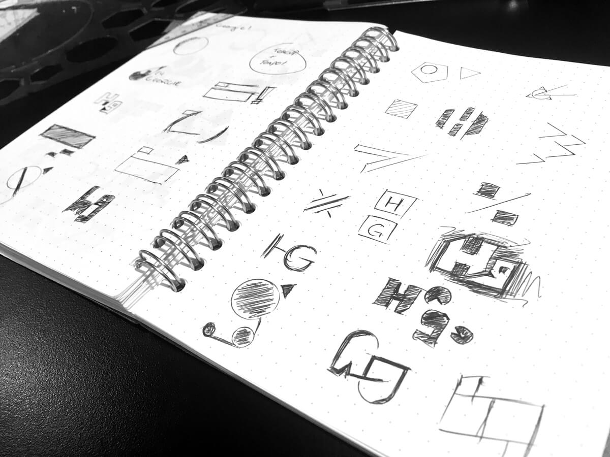 A dot grid spiral bound notebook with various logo sketches