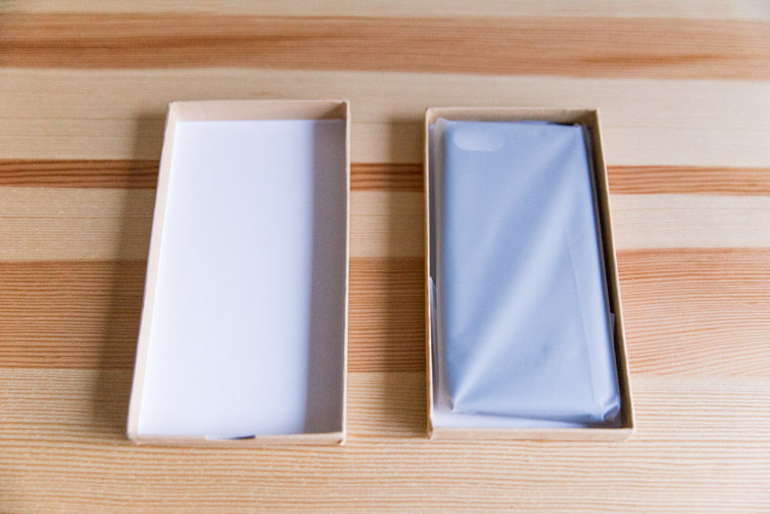 An open brown box and its lid, side by side. In the brown box is a phone case in transcluent plastic.