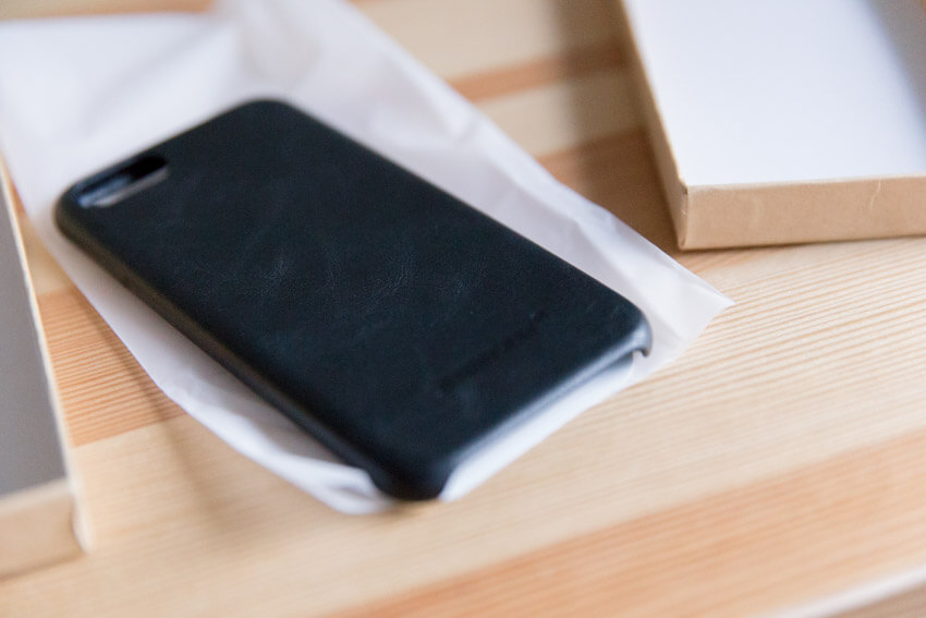 A black leather phone case, its back visible, on a piece of translucent plastic