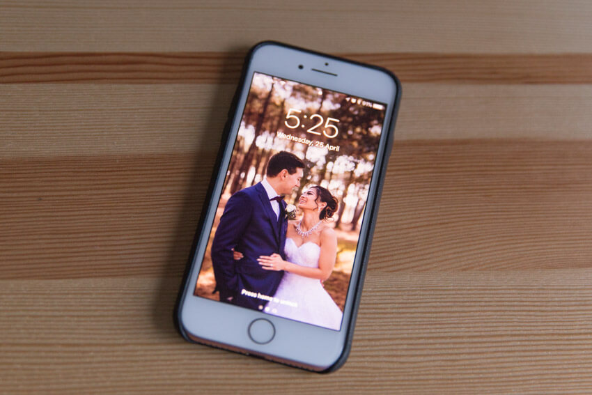 An iPhone with a black leather case, screen-up on a wooden surface, showing a man and woman in traditional wedding clothing on the screen