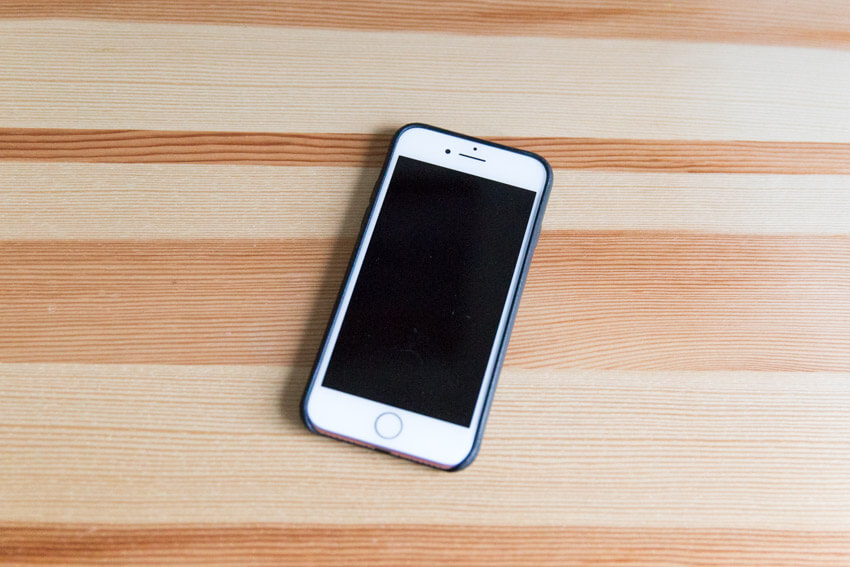 An iPhone with a black leather case, screen-up on a wooden surface
