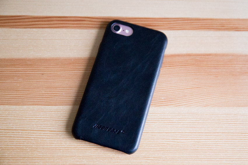 An iPhone with a black leather case, screen-down on a wooden surface