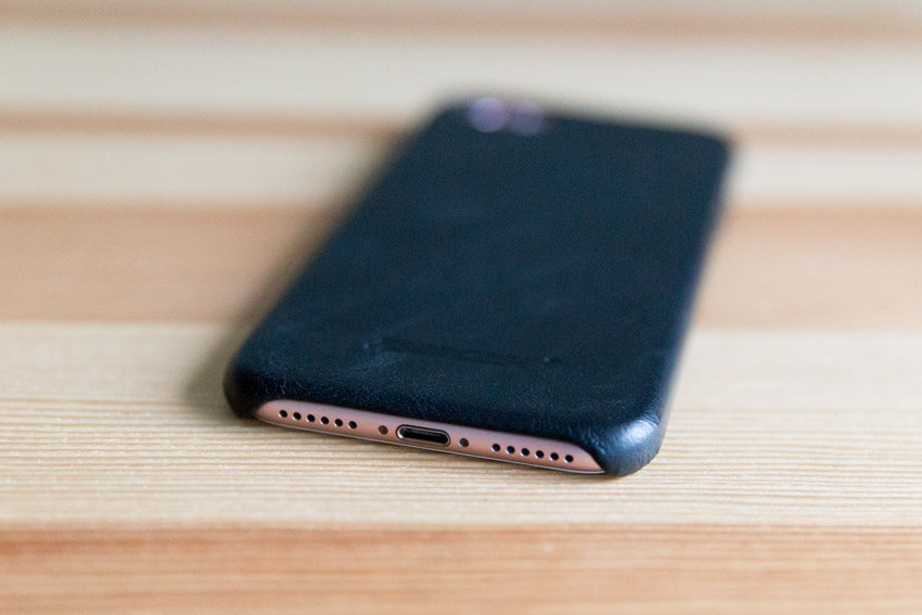 A view of the base of a pink iPhone with a black case with the speaker holes and charging port visible