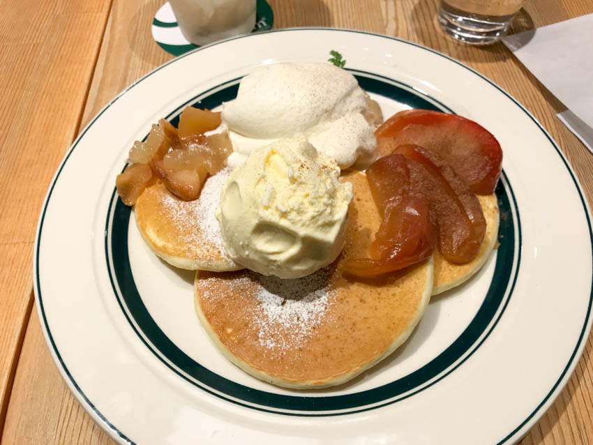 Plate is sweet pancakes with peach/apple and whipped cream