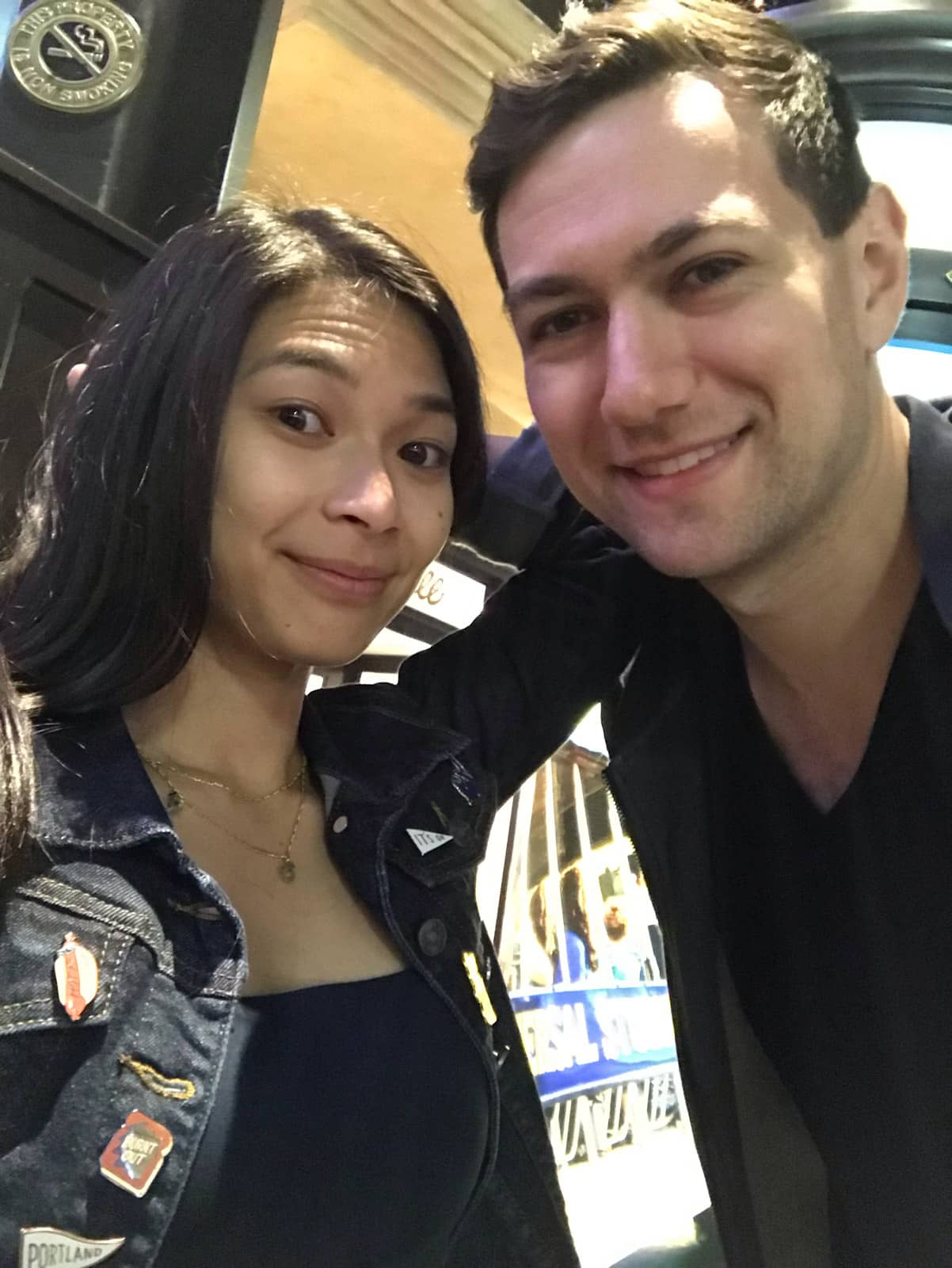 A man and woman taking a selfie and smiling. The woman is wearing a denim jacket with enamel pins and the man is wearing a dark v-neck shirt. The photo is taken in low lighting.