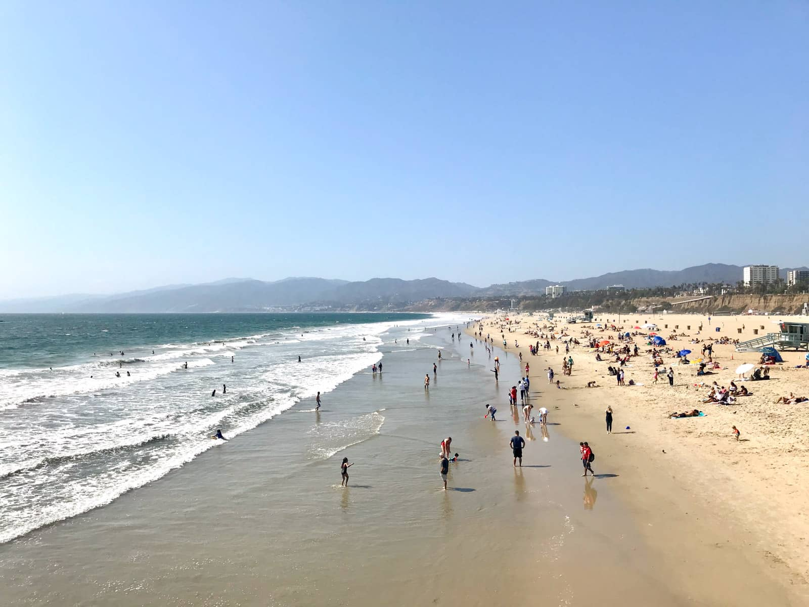Santa Monica Beach in Los Angeles, seen from the boardwalk. The sea is on the left had side and the sandy beach is on the right. The beach has many people standing in the shallow water and many with umbrellas and sitting on the sand