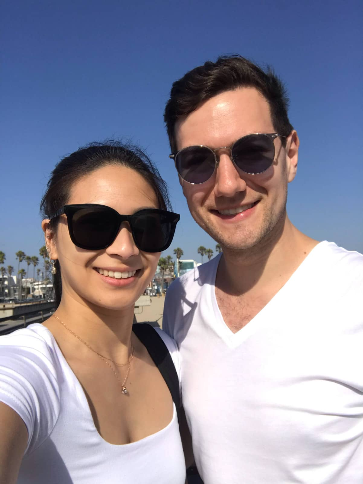 A selfie of a man and woman, both wearing white shirts and both wearing sunglasses