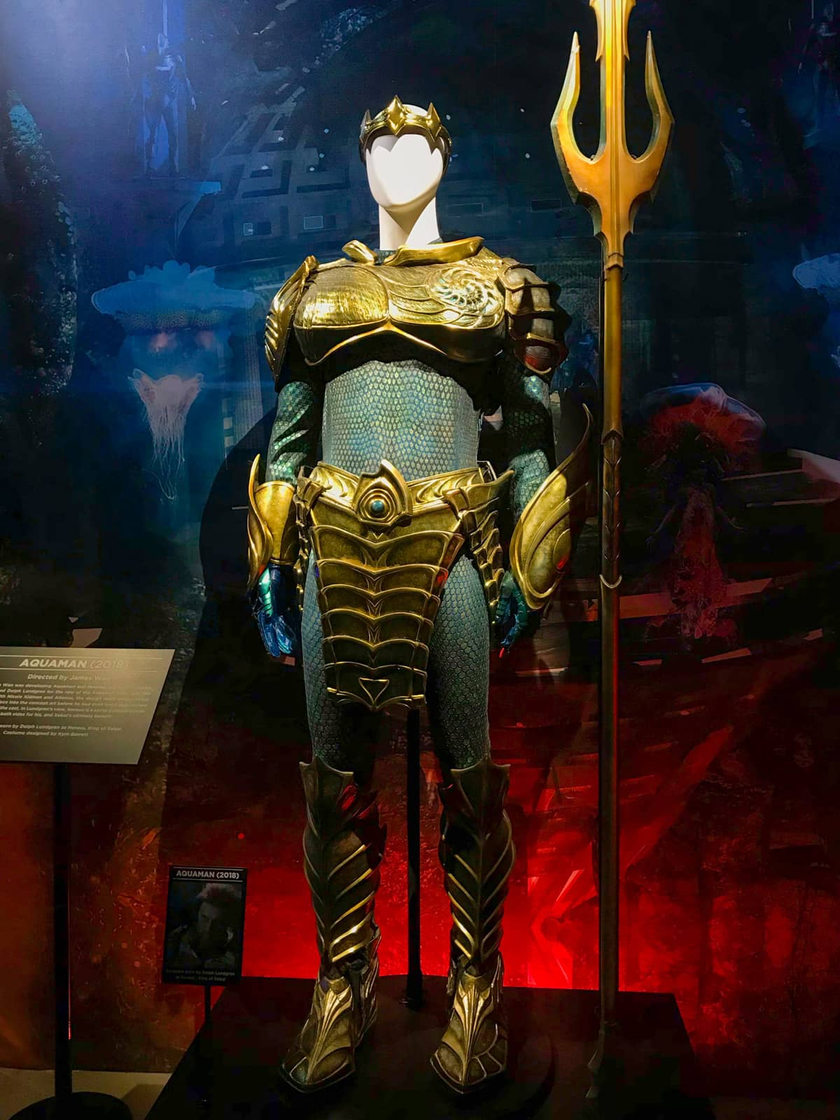An Aquaman costume on display on a mannequin. The cost is metallic blue and gold with shiny detail.  His trident stands next to him.