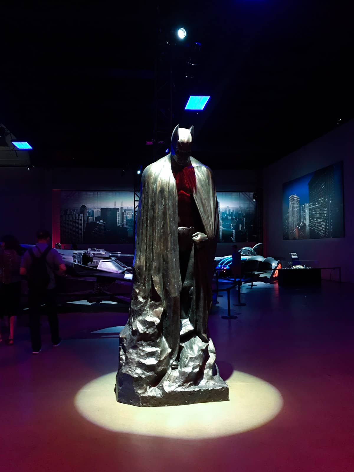 A dark room with a statue of the Batman character, with a spotlight light from above. Batman is looking down towards the ground. In the background are some automobiles