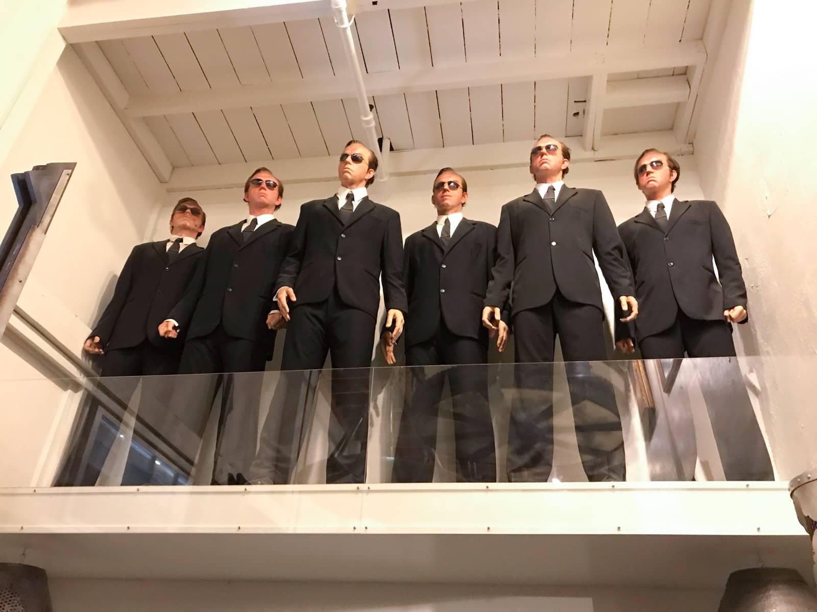 A prop of six men in suits and dark sunglasses made to resemble the same character