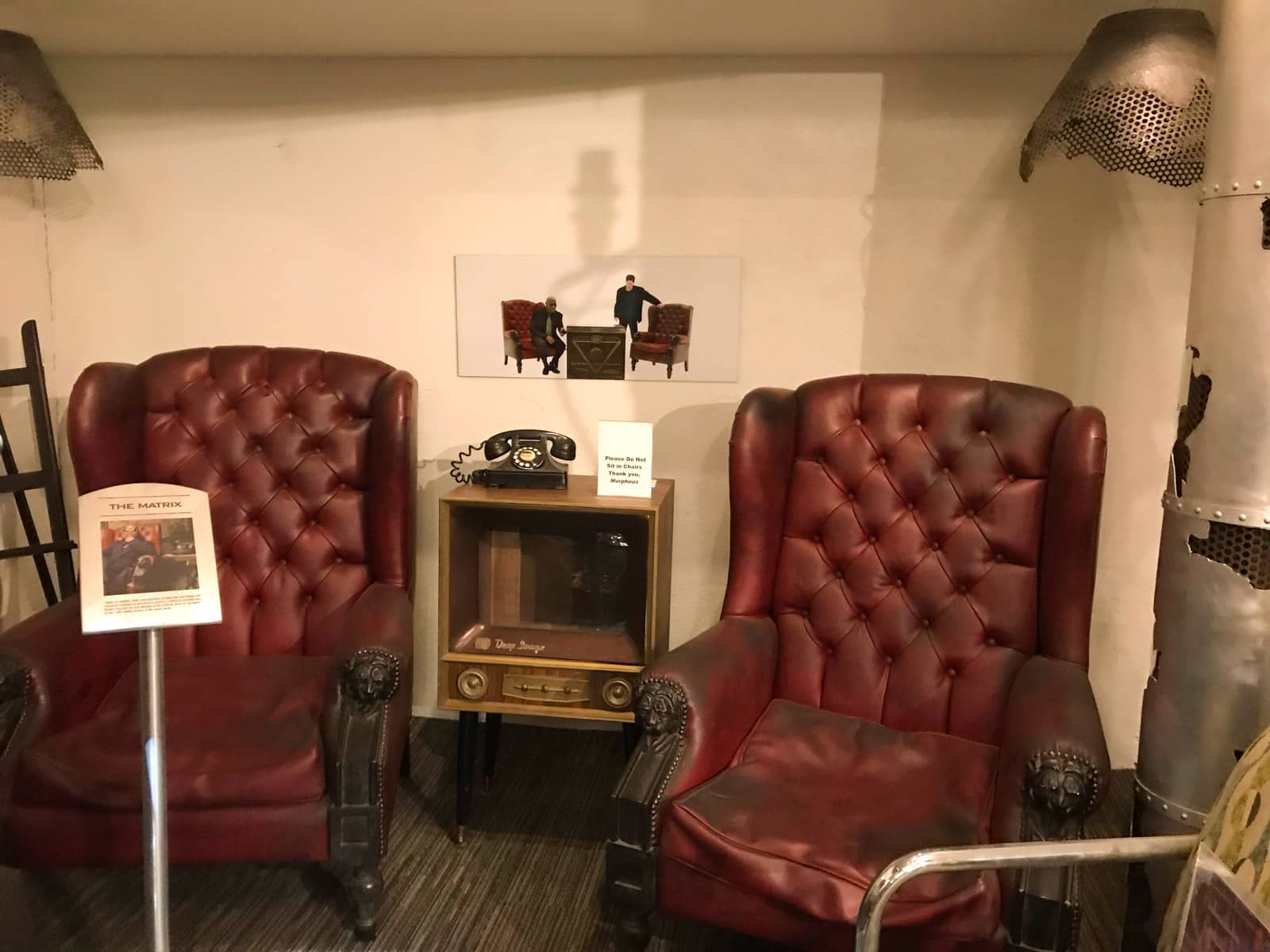 Two dark red leather chairs shown on display signage to be famous for their use the film The Matrix
