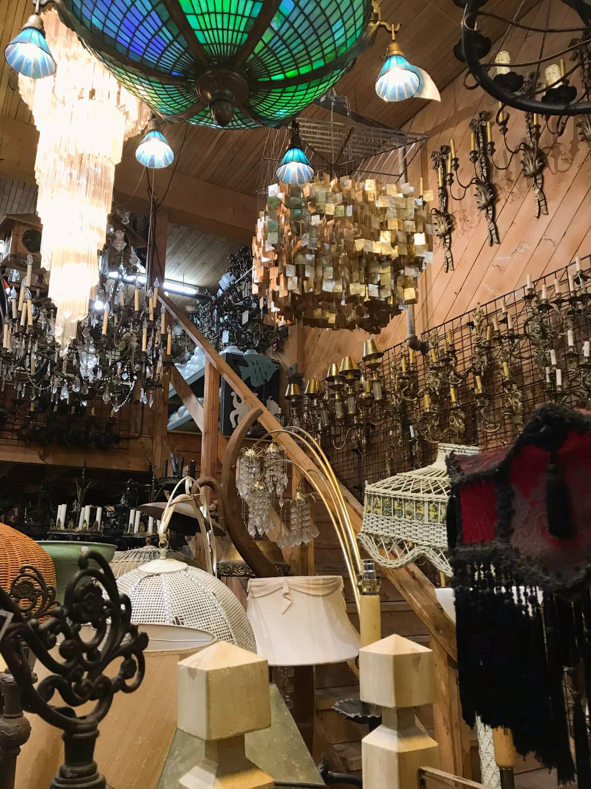 The inside of a props warehouse with many lanterns, chandeliers and other lighting.