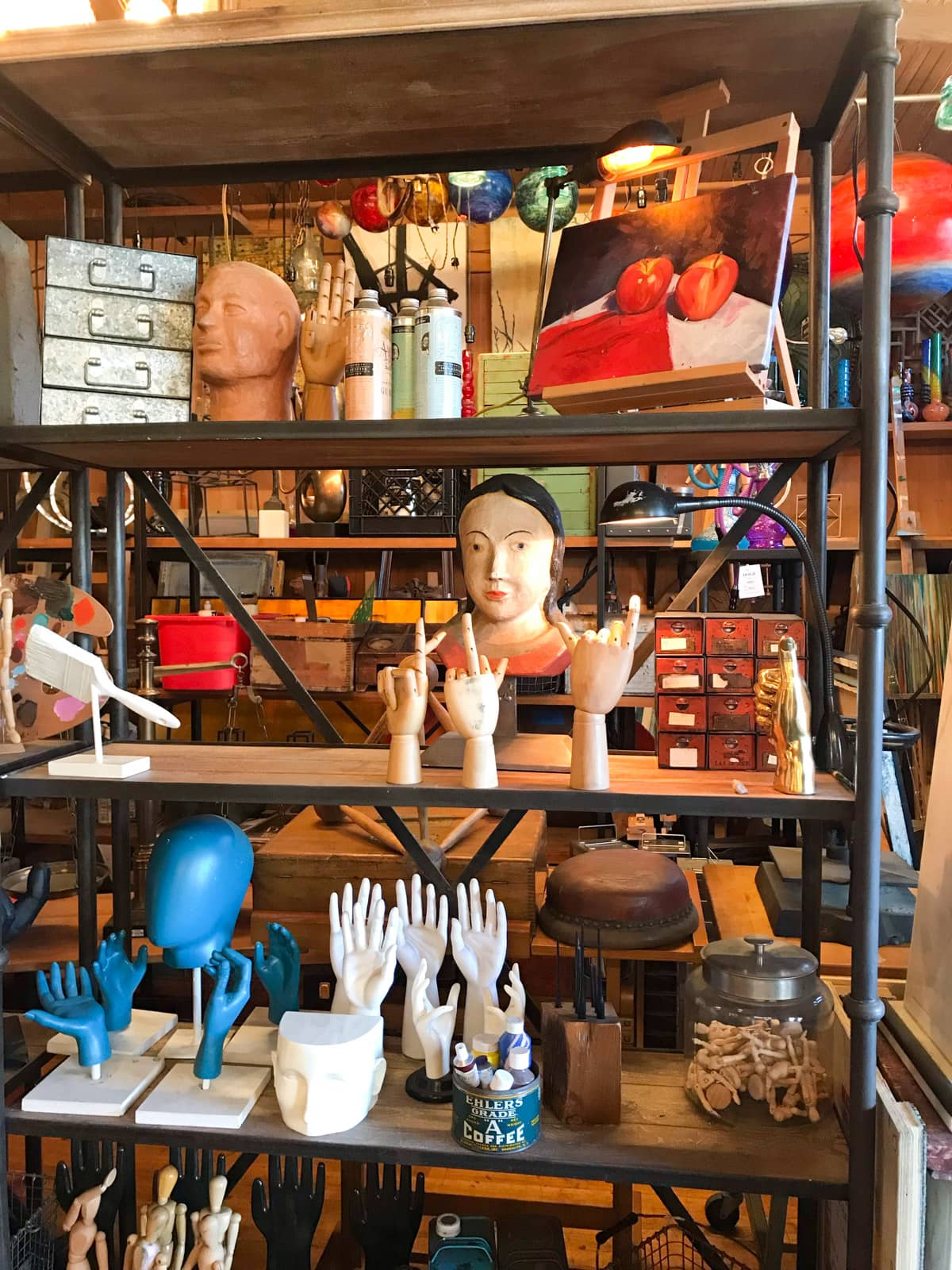 A shelf of many props, most of them being models of hands and heads. Shelves in the background are full as well.