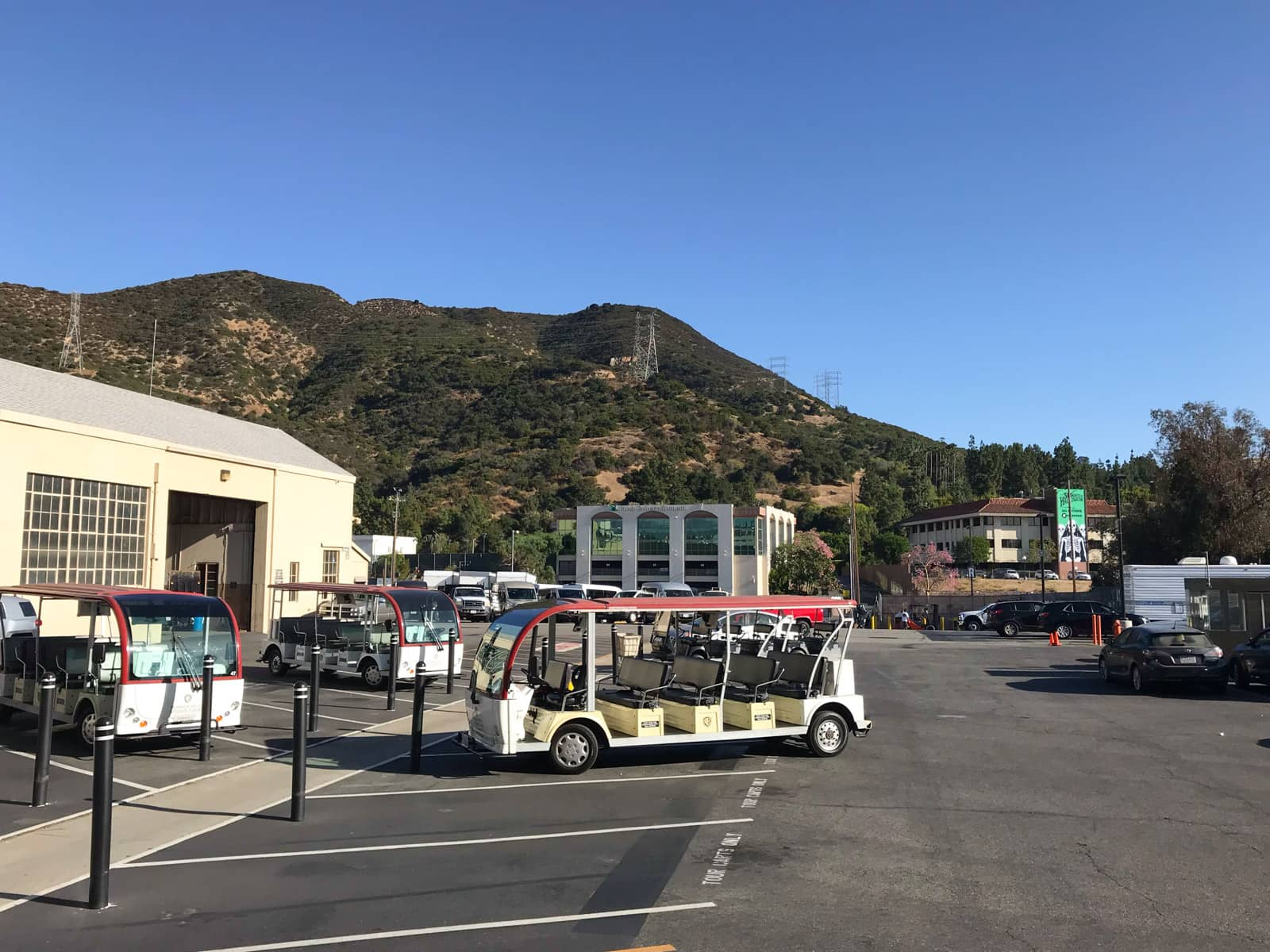 The outside of a film and television studio, with open passenger buses parked outside. In the background you can see the hills of Los Angeles, brown in colour but dotted with many trees.