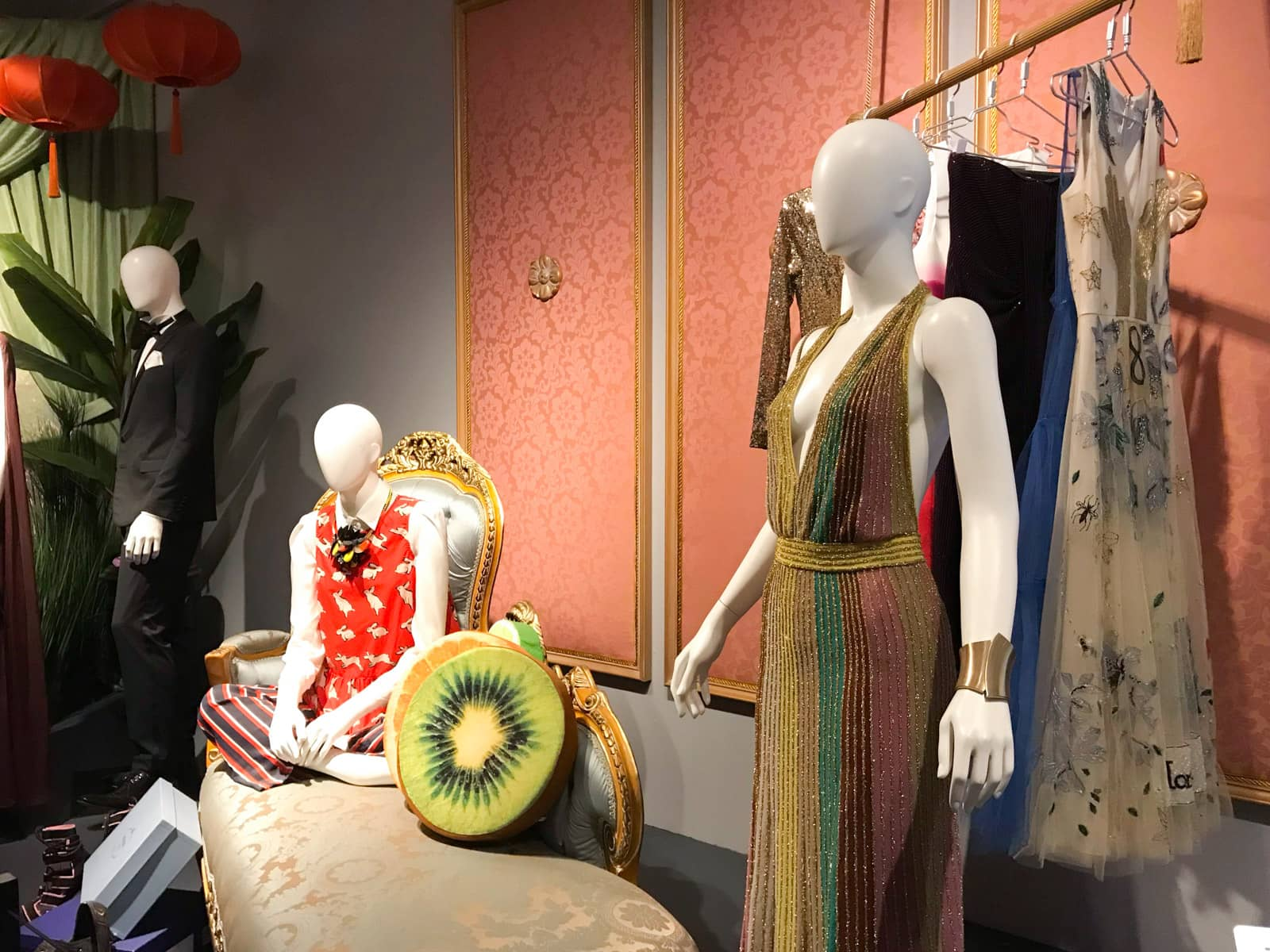 Mannequins on display with a couple of different characters, one sitting on a couch and the other in a ballgown. A rack of clothes stands behind one mannequin. There is a kiwi-fruit-styled cushion on the couch.
