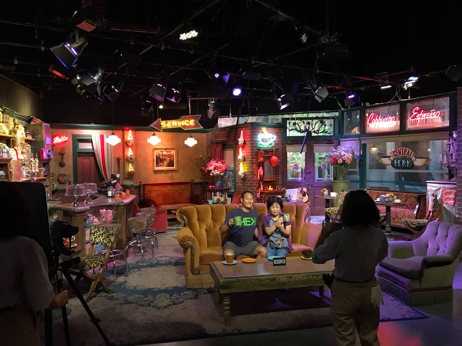 A television stage set with various props and neon signs. In the centre of frame is a large old couch with two people sitting in it, posed for a photo