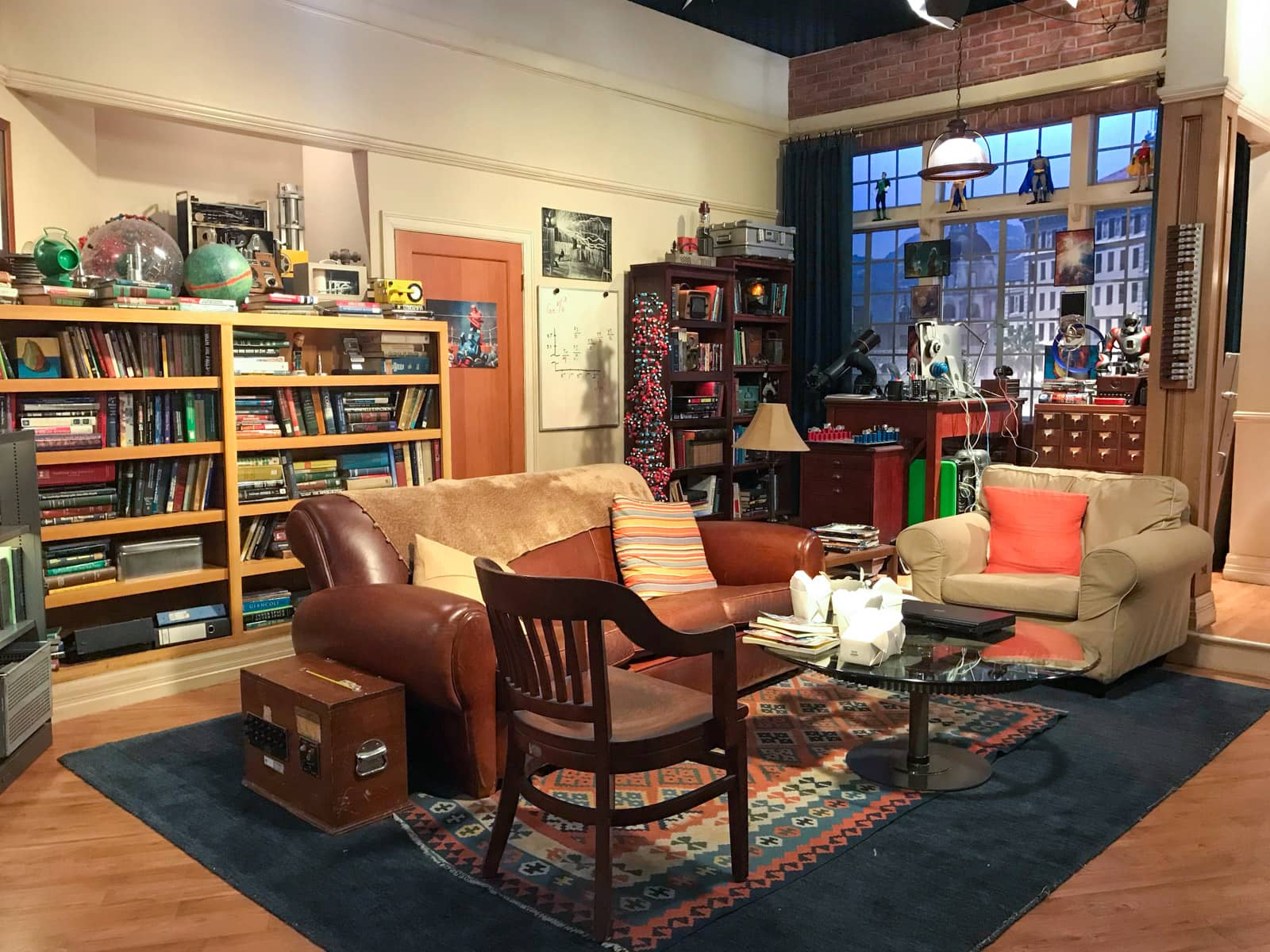 A television stage set up to look like a small apartment, with bookshelves full of books and a window looking out to the city.