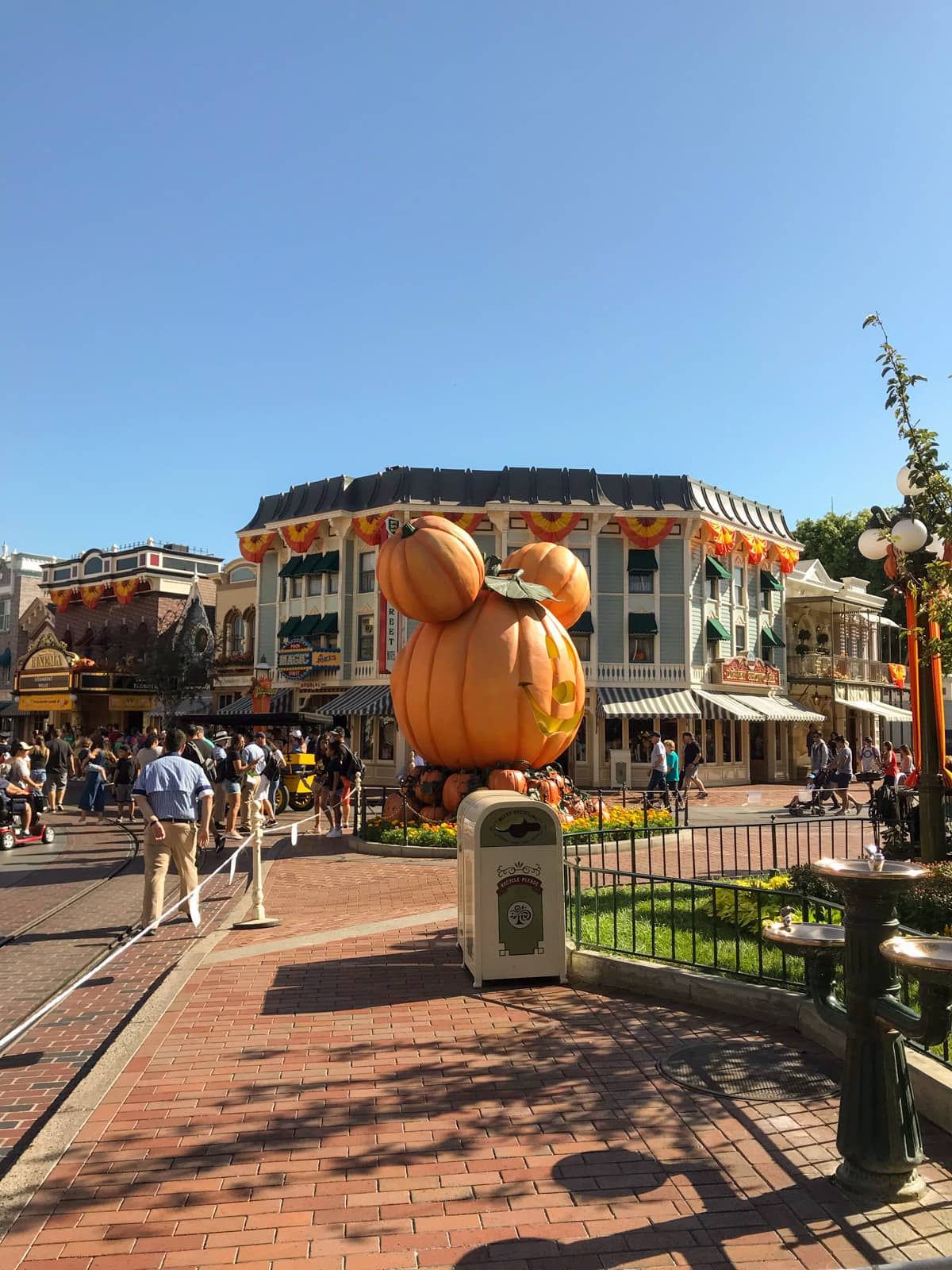 A view inside a Disneyland theme park, where a large statue of Mickey's head styled like a carved pumpkin is in the centre of the frame