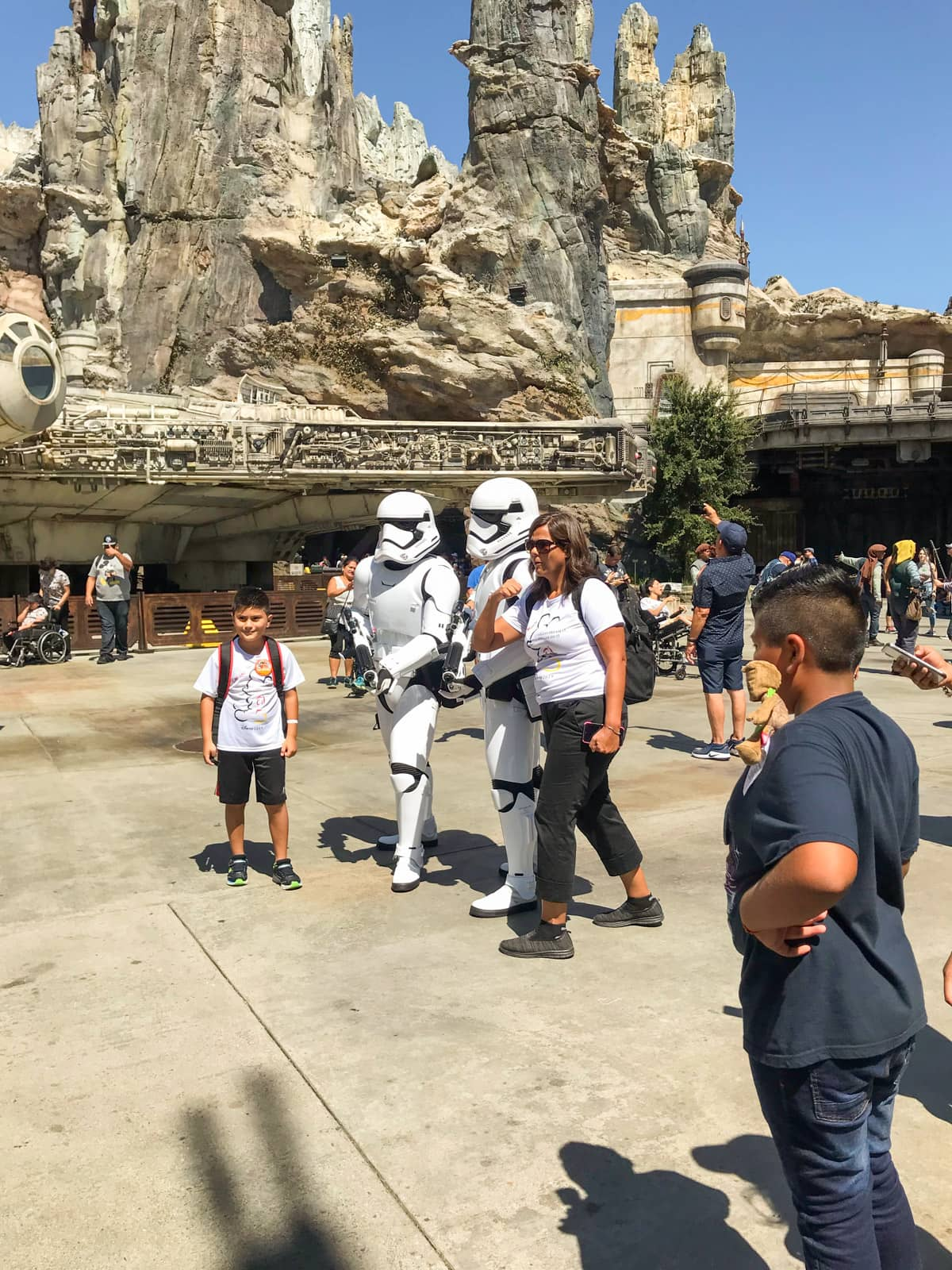 People dressed up in white astronaut-like costumes to resemble Stormtrooper characters from Star Wars, in a theme park with several people surrounding them to take photos with them