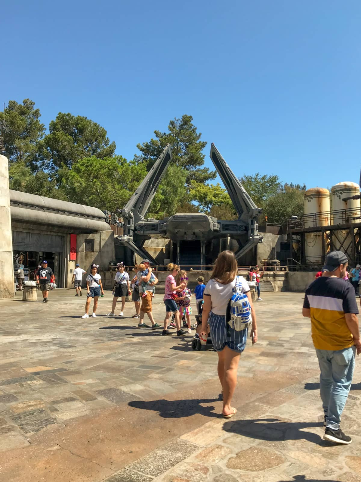 Some people walking around in an open area of a theme park, that is themed to look like a futuristic and earthy outer-space area.