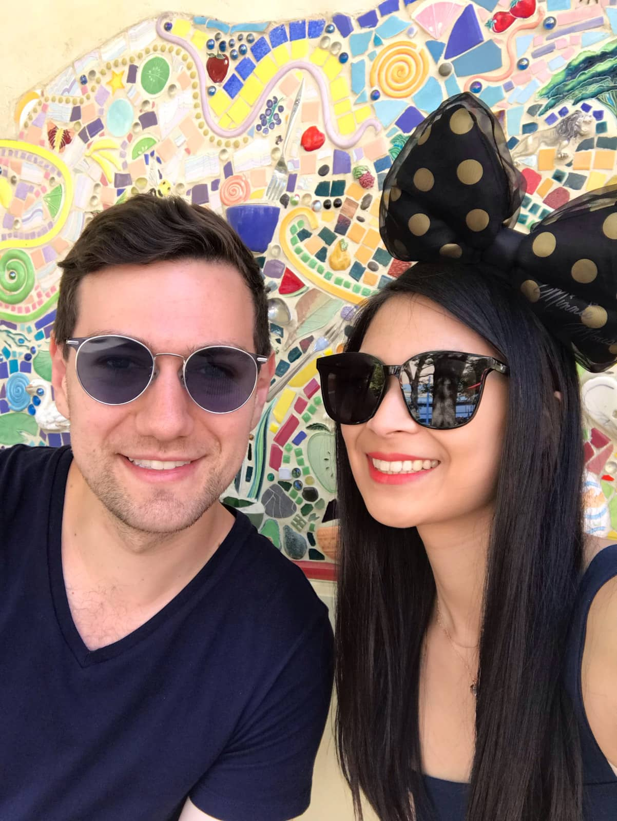 A man and woman in a selfie, in front of a colourful mosaic tile wall. They are both smiling and both wearing sunglasses. Both of them have dark hair. The woman is wearing a big bow on top of her head that is black with gold spots.