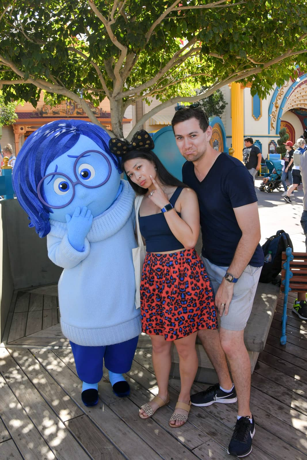 A man and woman posing with sad faces, alongside a person dressed in a character costume of Sadness from Pixar film Inside Out. Sadness' costume is different shades of blue with blue skin, blue glasses and blue hair.