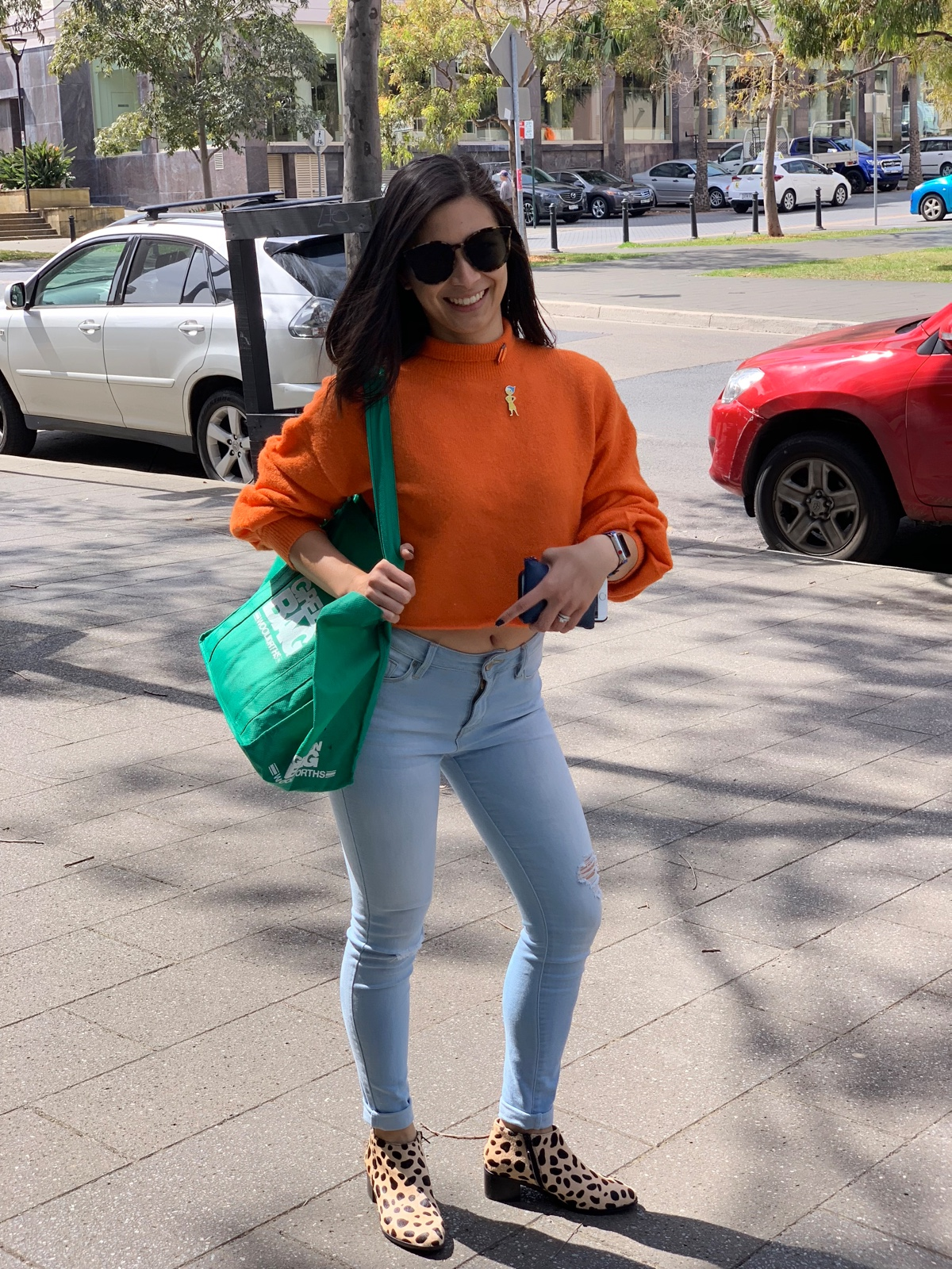 A woman with sunglasses wearing an orange sweater and light blue jeans. She is holding a green grocery bag over her arm.
