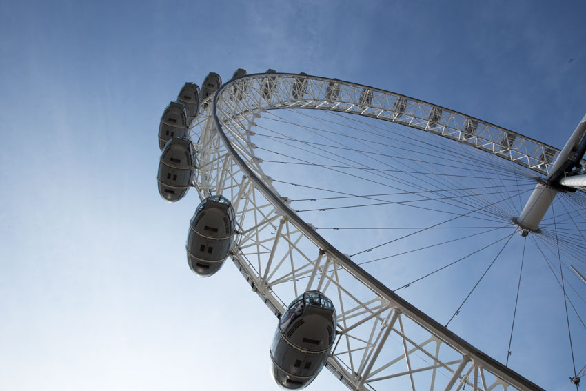Extreme low angle shot of London Eye ferris wheel with blue sky background